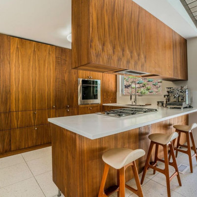 Example of a mid-sized 1950s terrazzo floor, white floor and exposed beam kitchen design in Los Angeles with a double-bowl sink, flat-panel cabinets, solid surface countertops, stainless steel appliances, a peninsula, white countertops and medium tone wood cabinets