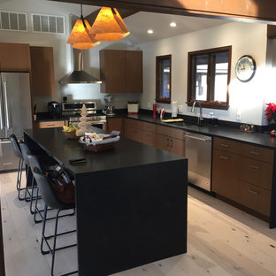 This is an example of a mid-sized midcentury l-shaped open plan kitchen in Other with quartz benchtops, a double-bowl sink, flat-panel cabinets, medium wood cabinets, stainless steel appliances, light hardwood floors, with island, beige floor and black benchtop.