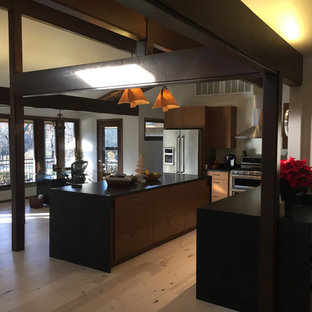 This is an example of a mid-sized midcentury l-shaped open plan kitchen in Other with a double-bowl sink, flat-panel cabinets, medium wood cabinets, quartz benchtops, stainless steel appliances, light hardwood floors, with island, beige floor and black benchtop.
