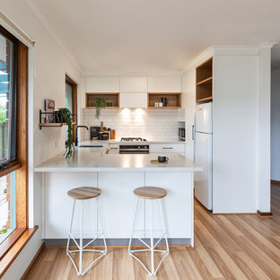 This is an example of a scandinavian u-shaped kitchen in Adelaide with an undermount sink, flat-panel cabinets, white cabinets, white splashback, subway tile splashback, white appliances, brown floor, white benchtop, quartz benchtops and laminate floors.