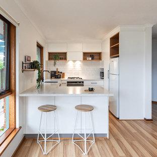 アデレードの北欧スタイルのおしゃれなコの字型キッチン (アンダーカウンターシンク、フラットパネル扉のキャビネット、白いキャビネット、白いキッチンパネル、サブウェイタイルのキッチンパネル、白い調理設備、茶色い床、白いキッチンカウンター、クオーツストーンカウンター、ラミネートの床) の写真