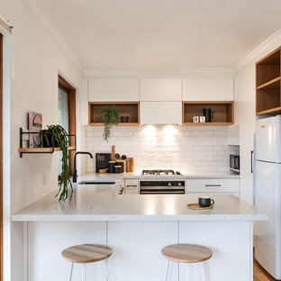 Contemporary u-shaped kitchen in Adelaide with an undermount sink, flat-panel cabinets, white cabinets, white splashback, white appliances, a peninsula, brown floor, white benchtop and laminate floors.