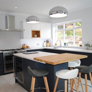 This is an example of a medium sized scandi u-shaped enclosed kitchen in Hertfordshire with a built-in sink, flat-panel cabinets, stainless steel appliances, an island, grey floors and white worktops.