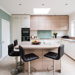 This is an example of a mid-sized contemporary l-shaped eat-in kitchen in Surrey with a single-bowl sink, flat-panel cabinets, light wood cabinets, laminate benchtops, green splashback, glass sheet splashback, black appliances, ceramic floors, with island, beige floor and beige benchtop.