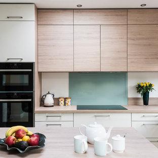 Photo of a scandi l-shaped kitchen/diner in Surrey with a single-bowl sink, flat-panel cabinets, light wood cabinets, laminate countertops, green splashback, glass sheet splashback, black appliances, ceramic flooring, an island, beige floors and beige worktops.