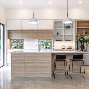 Design ideas for a mid-sized contemporary galley kitchen in Adelaide with an undermount sink, flat-panel cabinets, light wood cabinets, quartz benchtops, white splashback, subway tile splashback, stainless steel appliances, concrete floors, with island, grey floor and grey benchtop.