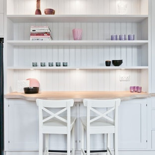 Photo of a scandi kitchen in London with shaker cabinets, white cabinets, wood worktops and light hardwood flooring.