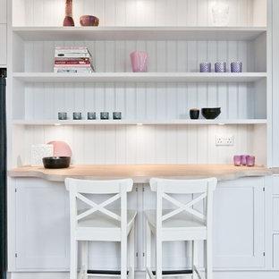 ロンドンの北欧スタイルのおしゃれなキッチン (シェーカースタイル扉のキャビネット、白いキャビネット、木材カウンター、淡色無垢フローリング) の写真