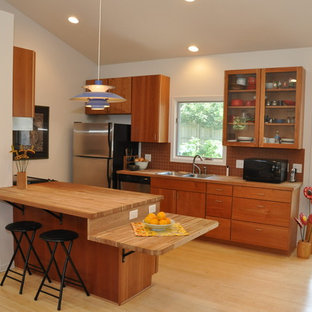 Inspiration for a small country galley open plan kitchen in Omaha with a double-bowl sink, flat-panel cabinets, medium wood cabinets, wood benchtops, orange splashback, terra-cotta splashback, stainless steel appliances, bamboo floors and a peninsula.