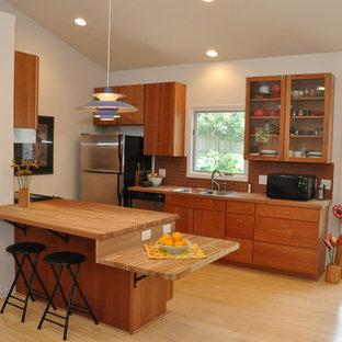 オマハの小さいカントリー風おしゃれなキッチン (ダブルシンク、フラットパネル扉のキャビネット、中間色木目調キャビネット、木材カウンター、オレンジのキッチンパネル、テラコッタタイルのキッチンパネル、シルバーの調理設備の、竹フローリング) の写真