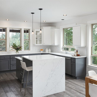 Large transitional eat-in kitchen photos - Example of a large transitional u-shaped dark wood floor and brown floor eat-in kitchen design in Portland with an undermount sink, shaker cabinets, gray cabinets, quartz countertops, white backsplash, stone slab backsplash, stainless steel appliances and an island