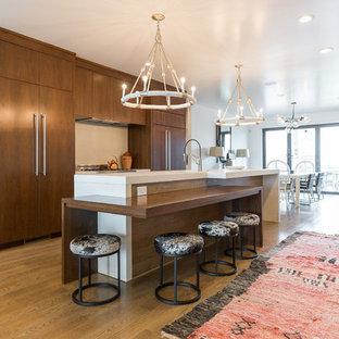 ウィルミントンの中サイズのコンテンポラリースタイルのおしゃれなキッチン (アンダーカウンターシンク、フラットパネル扉のキャビネット、濃色木目調キャビネット、コンクリートカウンター、白いキッチンパネル、セメントタイルのキッチンパネル、無垢フローリング、パネルと同色の調理設備、茶色い床) の写真
