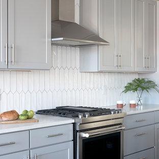 ポートランド(メイン)の小さい北欧スタイルのおしゃれなキッチン (シングルシンク、シェーカースタイル扉のキャビネット、グレーのキャビネット、クオーツストーンカウンター、白いキッチンパネル、セラミックタイルのキッチンパネル、シルバーの調理設備の、濃色無垢フローリング、茶色い床、白いキッチンカウンター) の写真