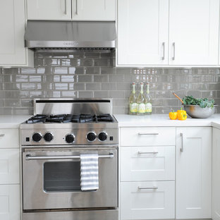 Inspiration for a small midcentury l-shaped eat-in kitchen in Vancouver with an undermount sink, shaker cabinets, white cabinets, solid surface benchtops, grey splashback, glass tile splashback, stainless steel appliances, porcelain floors and no island.
