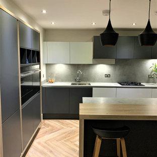 他の地域の小さい北欧スタイルのおしゃれなキッチン (ダブルシンク、フラットパネル扉のキャビネット、淡色木目調キャビネット、コンクリートカウンター、黒い調理設備、クッションフロア) の写真