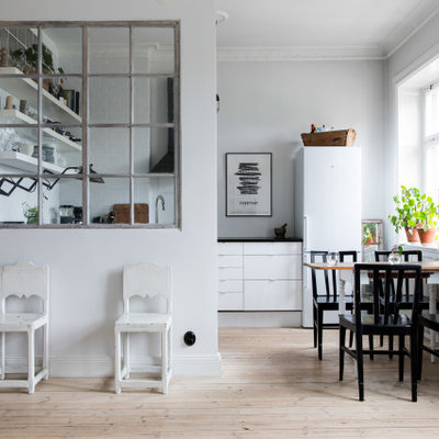 Eat-in kitchen - small scandinavian u-shaped light wood floor and beige floor eat-in kitchen idea in New York with flat-panel cabinets, white cabinets, white appliances, no island and black countertops