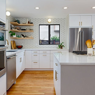 Small scandinavian eat-in kitchen designs - Small danish l-shaped medium tone wood floor and brown floor eat-in kitchen photo in Seattle with an undermount sink, flat-panel cabinets, white cabinets, quartz countertops, white backsplash, mosaic tile backsplash, stainless steel appliances, an island and white countertops