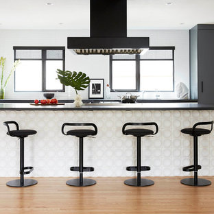 Small scandinavian open concept kitchen pictures - Small danish galley medium tone wood floor open concept kitchen photo in San Francisco with flat-panel cabinets, black countertops, an integrated sink and ceramic backsplash