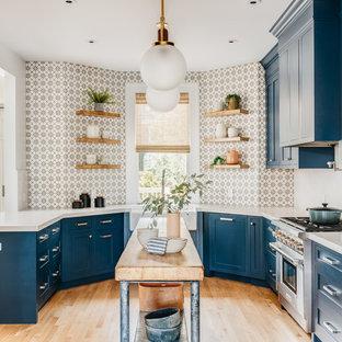 サンフランシスコの北欧スタイルのおしゃれなキッチン (エプロンフロントシンク、シェーカースタイル扉のキャビネット、青いキャビネット、マルチカラーのキッチンパネル、シルバーの調理設備の、淡色無垢フローリング、白いキッチンカウンター、ベージュの床) の写真