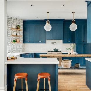 Skandinavische Küche in U-Form mit Schrankfronten im Shaker-Stil, blauen Schränken, Küchengeräten aus Edelstahl, hellem Holzboden, Kücheninsel, weißer Arbeitsplatte und bunter Rückwand in San Francisco