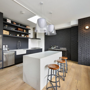 Scandinavian open concept kitchen remodeling - Open concept kitchen - scandinavian light wood floor open concept kitchen idea in New York with a farmhouse sink, open cabinets, black cabinets, black backsplash, stainless steel appliances and an island