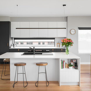 Inspiration for a scandinavian galley open plan kitchen in Hobart with a drop-in sink, flat-panel cabinets, white cabinets, medium hardwood floors, with island, brown floor and white benchtop.