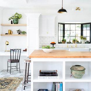 Foto di una cucina scandinava di medie dimensioni con lavello stile country, ante con riquadro incassato, ante bianche, paraspruzzi bianco, paraspruzzi con piastrelle diamantate, elettrodomestici in acciaio inossidabile, pavimento in gres porcellanato, penisola e top in legno