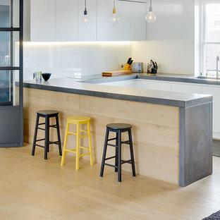 Выдающиеся фото от архитекторов и дизайнеров интерьера: п-образная кухня в скандинавском стиле с плоскими фасадами, белыми фасадами, столешницей из бетона, белым фартуком, фартуком из стекла, светлым паркетным полом и полуостровом
