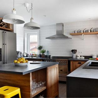 Idées déco pour une cuisine américaine scandinave en U de taille moyenne avec un évier posé, un placard avec porte à panneau surélevé, des portes de placard en bois brun, un électroménager en acier inoxydable, un sol en bois brun, un îlot central, une crédence blanche et une crédence en bois.