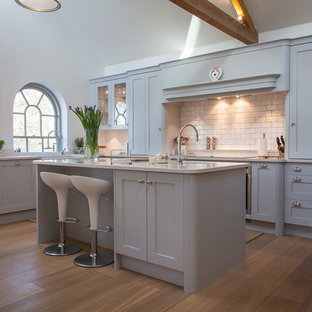 Inspiration for a medium sized rural l-shaped kitchen/diner in Hertfordshire with a belfast sink, shaker cabinets, grey cabinets, engineered stone countertops, white splashback, metro tiled splashback, stainless steel appliances, medium hardwood flooring, an island, brown floors and grey worktops.