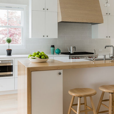 Inspiration for a scandinavian light wood floor kitchen remodel in Boston with an undermount sink, flat-panel cabinets, white cabinets, wood countertops and gray backsplash