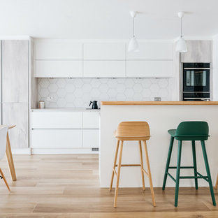 Inspiration for a large scandinavian galley kitchen/diner in Cambridgeshire with flat-panel cabinets, white splashback, ceramic splashback, integrated appliances, ceramic flooring, a breakfast bar, brown floors, white cabinets, wood worktops and beige worktops.