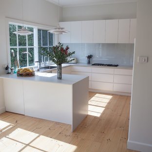 Mid-sized scandinavian eat-in kitchen appliance - Inspiration for a mid-sized scandinavian u-shaped light wood floor eat-in kitchen remodel in Melbourne with flat-panel cabinets, white cabinets, a peninsula, an undermount sink, granite countertops, white backsplash, glass sheet backsplash, stainless steel appliances and gray countertops