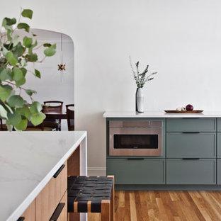 ナッシュビルの中サイズの北欧スタイルのおしゃれなキッチン (アンダーカウンターシンク、フラットパネル扉のキャビネット、黄色いキャビネット、クオーツストーンカウンター、白いキッチンパネル、石スラブのキッチンパネル、シルバーの調理設備の、無垢フローリング、オレンジの床、白いキッチンカウンター) の写真