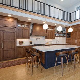 Inredning av ett klassiskt stort vit vitt l-kök, med en undermonterad diskho, luckor med profilerade fronter, vitt stänkskydd, stänkskydd i tunnelbanekakel, mellanmörkt trägolv, en köksö, brunt golv och skåp i mellenmörkt trä