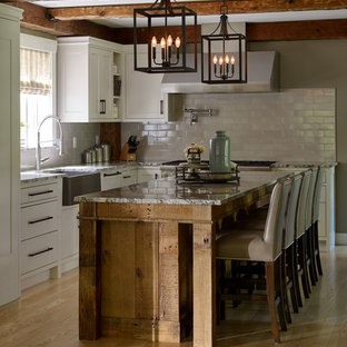 Inspiration for a large country eat-in kitchen in Portland Maine with a farmhouse sink, shaker cabinets, white cabinets, granite benchtops, grey splashback, subway tile splashback, panelled appliances, light hardwood floors, with island, multi-coloured benchtop and beige floor.