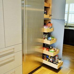 ニューヨークの広いコンテンポラリースタイルのおしゃれなキッチン (アンダーカウンターシンク、ガラス扉のキャビネット、淡色木目調キャビネット、ガラスカウンター、白いキッチンパネル、ガラスタイルのキッチンパネル、シルバーの調理設備、淡色無垢フローリング) の写真