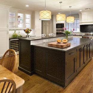Inredning av ett klassiskt avskilt, stort svart svart u-kök, med skåp i shakerstil, rostfria vitvaror, en undermonterad diskho, vita skåp, mellanmörkt trägolv, en köksö, brunt golv, granitbänkskiva, grått stänkskydd och stänkskydd i glaskakel