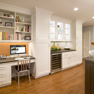 ニューヨークの大きいトランジショナルスタイルのおしゃれなキッチン (シェーカースタイル扉のキャビネット、白いキャビネット、アンダーカウンターシンク、白いキッチンパネル、大理石の床、シルバーの調理設備の、無垢フローリング、茶色い床、御影石カウンター、黒いキッチンカウンター) の写真