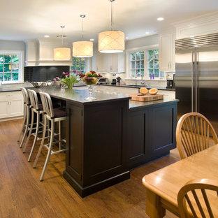 ニューヨークの大きいトランジショナルスタイルのおしゃれなキッチン (シェーカースタイル扉のキャビネット、アンダーカウンターシンク、シルバーの調理設備の、無垢フローリング、茶色い床、白いキャビネット、御影石カウンター、グレーのキッチンパネル、ガラスタイルのキッチンパネル、黒いキッチンカウンター) の写真