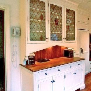 ニューヨークの中サイズのヴィクトリアン調のおしゃれなキッチン (アンダーカウンターシンク、インセット扉のキャビネット、白いキャビネット、木材カウンター、茶色いキッチンパネル、木材のキッチンパネル、シルバーの調理設備の、濃色無垢フローリング、アイランドなし、茶色い床、茶色いキッチンカウンター) の写真