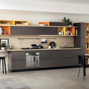 モントリオールの中サイズのモダンスタイルのおしゃれなダイニングキッチン (フラットパネル扉のキャビネット、グレーのキャビネット、木材カウンター、セラミックタイルのキッチンパネル、シルバーの調理設備の、セラミックタイルの床) の写真