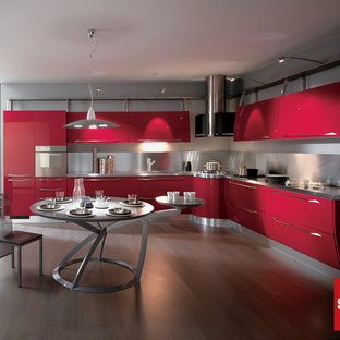 Large modern eat-in kitchen ideas - Eat-in kitchen - large modern l-shaped medium tone wood floor eat-in kitchen idea in Montreal with flat-panel cabinets, red cabinets, stainless steel countertops, metallic backsplash, metal backsplash, stainless steel appliances and a peninsula