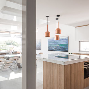 Design ideas for a contemporary l-shaped open plan kitchen in Perth with an undermount sink, light wood cabinets, marble benchtops, black appliances, ceramic floors, with island, grey floor, white benchtop, flat-panel cabinets and window splashback.