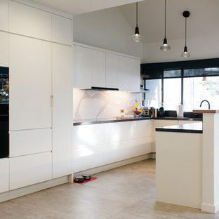 This is an example of a mid-sized modern u-shaped open plan kitchen in Salt Lake City with flat-panel cabinets, white cabinets, solid surface benchtops, white splashback, stone slab splashback, black appliances, ceramic floors and with island.