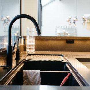 ソルトレイクシティの中サイズのモダンスタイルのおしゃれなキッチン (ダブルシンク、フラットパネル扉のキャビネット、白いキャビネット、茶色いキッチンパネル、モザイクタイルのキッチンパネル、黒い調理設備、セラミックタイルの床) の写真