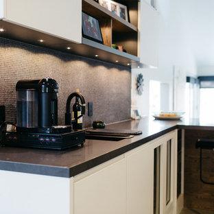 ソルトレイクシティの中くらいのモダンスタイルのおしゃれなキッチン (ダブルシンク、フラットパネル扉のキャビネット、白いキャビネット、茶色いキッチンパネル、モザイクタイルのキッチンパネル、黒い調理設備、セラミックタイルの床) の写真