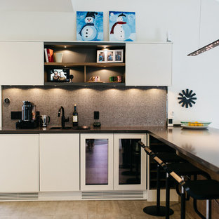 Inspiration for a mid-sized modern u-shaped open plan kitchen in Salt Lake City with flat-panel cabinets, white cabinets, zinc benchtops, black appliances, ceramic floors, with island, a double-bowl sink, brown splashback and mosaic tile splashback.