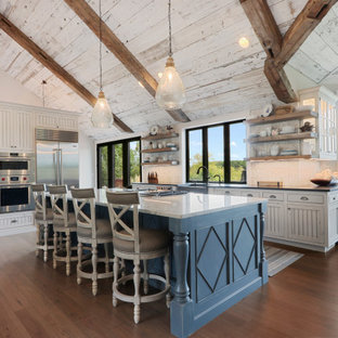 Country l-shaped open plan kitchen in Other with blue cabinets, ceramic splashback, stainless steel appliances, medium hardwood floors, multi-coloured benchtop, a farmhouse sink, louvered cabinets, white splashback, with island and brown floor.