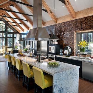 サクラメントの大きいインダストリアルスタイルのおしゃれなキッチン (アンダーカウンターシンク、フラットパネル扉のキャビネット、黒いキャビネット、茶色いキッチンパネル、シルバーの調理設備、無垢フローリング、モザイクタイルのキッチンパネル) の写真